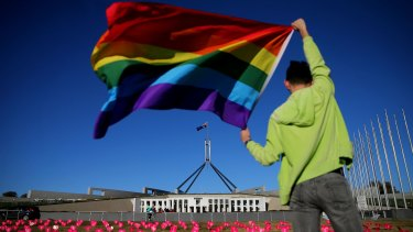 Marriage equality advocate Russell Nankervis poses with the rainbow flag during a 'Sea of Hearts' event in support of marriage equality on the front lawn of Parliament House.