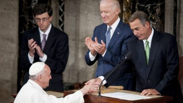 US Vice President Joseph Biden, centre, applauds as House Speaker John Boehner, right, greets Pope Francis as he arrives to speak to Congress in the House Chamber at the US Capitol.