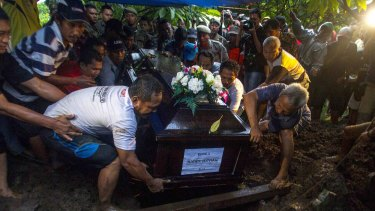 The coffin of Hayati Lutfiah Hamid is lowered in a funeral in the suburb of Desa Sawotratap.