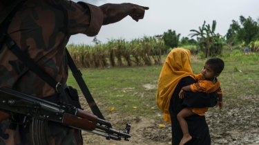 A Bangladeshi border guard sends a Rohingya woman and child back to their makeshift camp along the border with Myanmar last month.