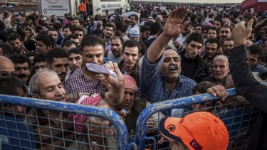 Syrian Kurdish refugees press against a gate as they hope to be allowed into Turkey.