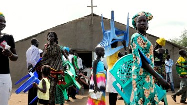 South Sudanese attend a Sunday service in Mingkaman. People bring their own chairs, a scarce commodity.