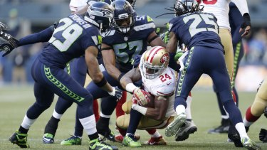 Brought down: San Francisco 49ers running back Shaun Draughn is tackled by the Seattle defence.