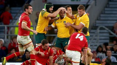 Tough times: Australian players celebrate after winning a penaty to relieve Welsh pressure on their tryline.
