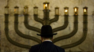 An Jewish man stands in front a menorah on the third eve of Hanukkah, at the Western Wall, in Jerusalem's old city.