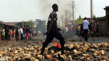 A man walks through paving stones and a tyre fire during protests against the governing party  in Bujumbura, Burundi, on June 26, 2015.