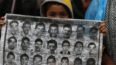 Dubious treatment: A boy holds up a sheet of photos showing some of the missing 43 students at the Independence monument in Mexico City.