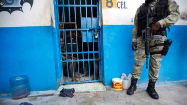 A police officer stands outside a room of inmates after a prison break at the Civil Prison in the coastal town of Arcahaiea, Haiti.