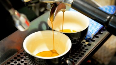 Espresso pours from a machine into cups during a class at the Barista Basics Coffee Academy in Sydney.