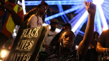 A demonstrator holds a sign during a protest in Atlanta in response to the police shooting deaths of Terence Crutcher in Tulsa and Keith Lamont Scott in Charlotte.