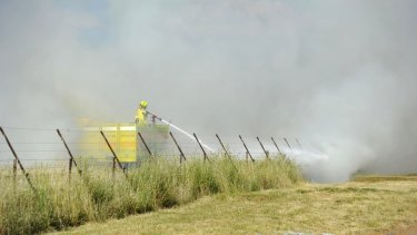 Fire crews put out a small grass fire on majura road near the airport in November 2014.