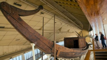 Tourists inspect King Khufu's first boat, which is displayed at the boat museum at the pyramids site in Giza.