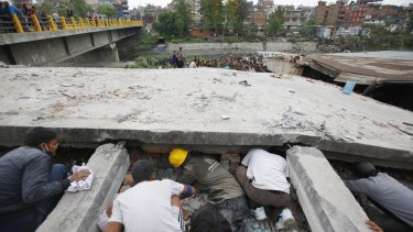 Rescuers look for victims under a collapsed building in Kathmandu.