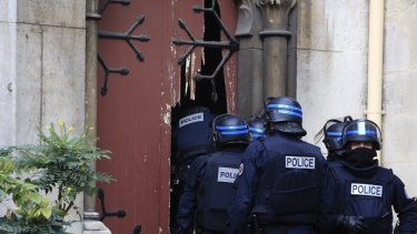 French police officers storm a church after a raid in Paris suburb Saint Denis.