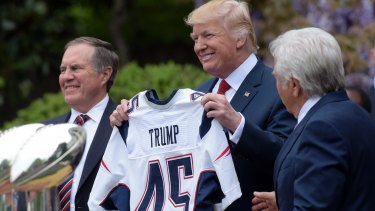 President Donald Trump holds up a New England Patriots jersey presented to him by Patriots owner Robert Kraft, right, and head coach Bill Belichick during a ceremony on the South Lawn of the White House on April 19, 2017.