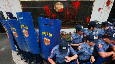 Riot police stand guard in front of the US embassy in Manila after protesters threw red paint as they forced their way closer to the embassy gates.