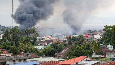 Fires rage following airstrikes by the Philippines Air Force in Marawi city on Saturday.