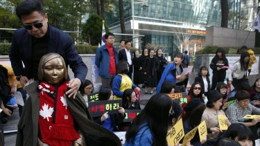 An activist puts his coat around the shoulders of the statue symbolising women and girls forced into sex slavery by the Japanese. The statue was placed outside the Japanese embassy in Seoul   in 2011.