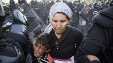 A woman and child flee as police respond with force against migrants protesting on the Serbia-Hungary border after they pushed through the border fence into Hungary.