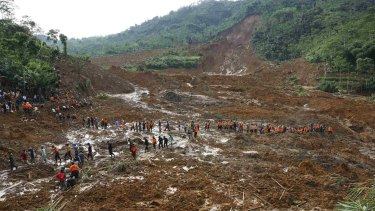 Search for survivors: Indonesian soldiers and rescue team members walk through the mud.