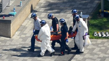 Police forensics carry a body bag on a stretcher out of the Grenfell Tower block.