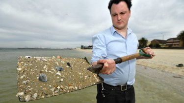 Michael Bourke with sand at Middle Park beach. Each grain of sand would host hundreds of micro-algae.