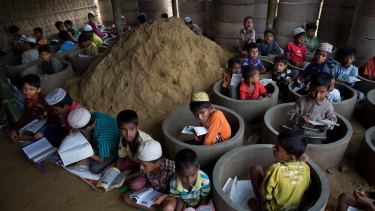 Rohingya children attend class amid material stocked for constructing latrines in Balukhali refugee camp, Bangladesh.