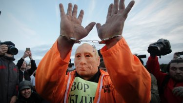 A protester wearing a mask depicting Russian President Vladimir Putin attends a rally in St Petersburg at the weekend.