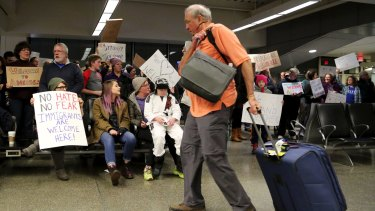 Travellers arriving  at the international gate of  Minneapolis-St Paul International Airport are greeted by protesters.