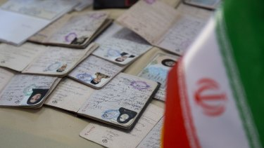 Identification is seen as voters cast their ballots at a polling station for the presidential election in Iran.