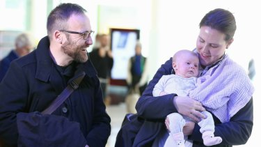 New father Greens MP Adam Bandt greets Ms O'Dwyer and Olivia at Canberra Airport, arriving for the return of Parliament this week.