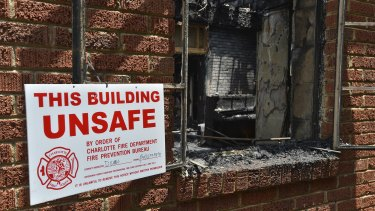 A sign warning the building is unsafe hangs outside the charred remains of Briar Creek Road Baptist Church.