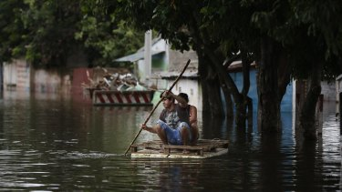 A couple drive a makeshift raft on a flooded street in Asuncion, Paraguay.