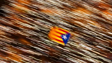 An independence flag is waved in Barcelona as demonstrators take part in a protest calling for the release of jailed Catalan politicians.