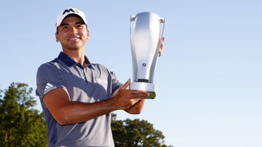 Jason Day celebrates with the winner's trophy.