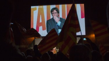 Ousted Catalan president Carles Puigdemont sends a kiss to his supporters as he appears via video link from Brussels on Tuesday.