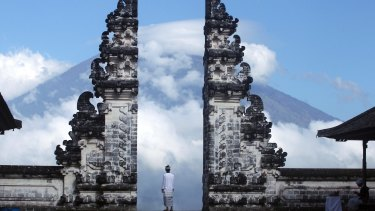 A Balinese man watches Mount Agung volcano almost covered with clouds as he stands at a temple in Karangasem.