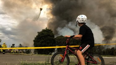 Luke, aged 11, watches the fires as they burn near his home.