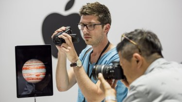 Event attendees take photographs of the new Apple iPad Pro.