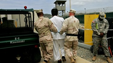 A Guantanamo prisoner escorted by US military personnel at the Guantanamo prison in 2007.