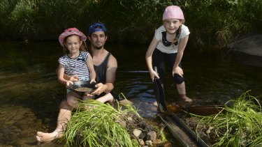 Golden dreams: Colin Adams pans for gold with his daughters, Lily, 6, and Brianna, 9.