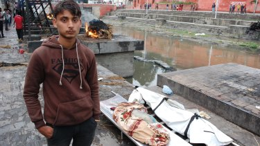 Jagat Nath Thakur, 19, stands with the body of his sister, 9, and nephew, 10, killed when a building collapsed during the Nepalese earthquake.