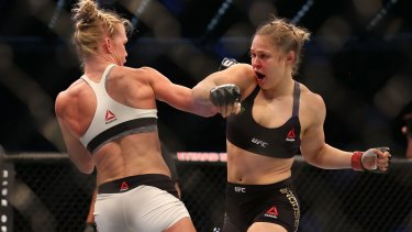 Failed defence: Favourite Ronda Rousey (right) had no answers for Holly Holm (left), losing her UFC world bantamweight title.