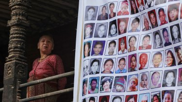 A Nepalese woman stands near photographs of victims of the 2015 earthquakes during a rally in Bhaktapur, Nepal.