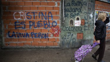 """""""All possibilities are open"""": A pedestrian passes graffiti that reads """"Cristina is the people"""" and """"Long live Peron"""" in the Mataderos neighbourhood of Buenos Aires."""