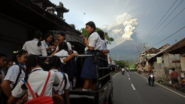 Students go to school as Mount Agung spews smoke and ash in Bali on November 28, 2017.