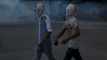 A Kashmiri protester holds a brick before throwing it at Indian police in Srinagar, Indian-controlled Kashmir.