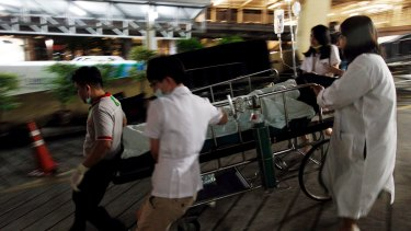Medical workers rush the victim of a blast at the Erawan Shrine to a nearby hospital in central Bangkok on Monday.