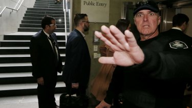 An AFP officer waves away press photographers as Senator Stephen Conroy's staff arrive at Parliament House on Wednesday.