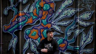 Social entrepreneur Ben Hoban wears a hoodie with a print of actual artwork of a sea dragon by artist Facter on the wall of Flinders Court, a laneway between Flinders Lane and Flinders Street.